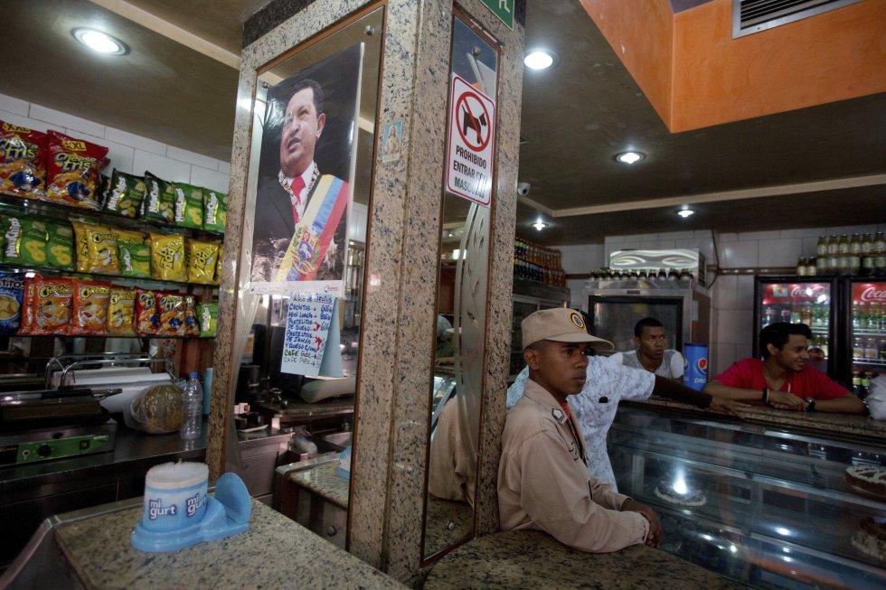 Miembro de la milicia hace guardia en una panadería privada tomada por el Gobierno. Después, los nuevos gestores del establecimiento retiraron cartel publicitario de Coca-Cola y adornaron las paredes con fotos del presidente Nicolás Maduro, de Chávez y del Libertador Simón Bolívar.
