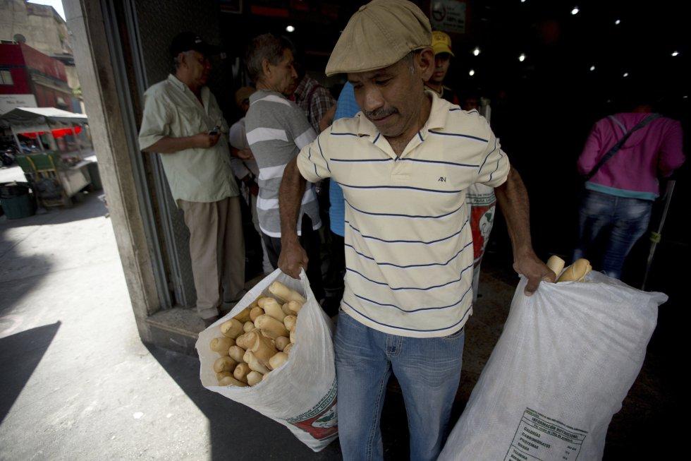 Un empleado de la panadería estatal Minka carga bolsas con pan para su distribución en tiendas estatales, en Caracas, Venezuela.