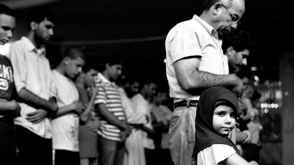 """La exposición continuará abierta al público hasta el 30 de julio. En la foto: """"Chica joven en oraciones con su padre"""", en la Sociedad Musulmana Americana, Brooklyn, 2010."""