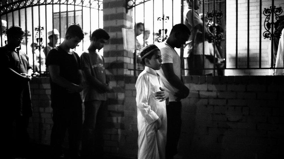 """En Nueva York hay casi 300 mezquitas, según estudios recientes. En la foto: """"Niño rezando durante el Ramadán en la calle fuera de la mezquita porque la mezquita está llena"""", Parkchester Jame Masjid, en el Bronx, 2012."""
