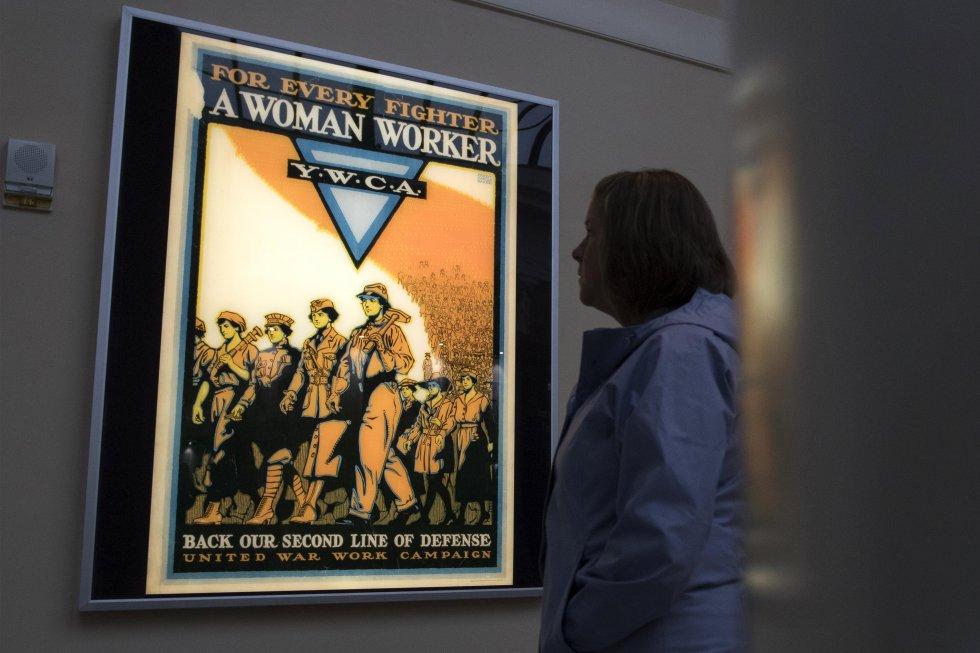 Una mujer observa un cartel de reclutamiento de la I Guerra Mundial de la organización YWCA.