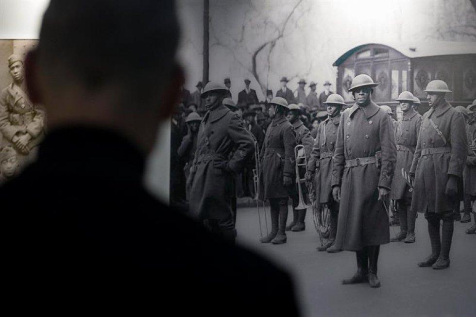 Un hombre observa unas fotos en blanco y negro del teniente James Reese Europe (Centro) y su escuadrón de infantería 369, junto a varios soldados afroamericanos de la I Guerra Mundial.