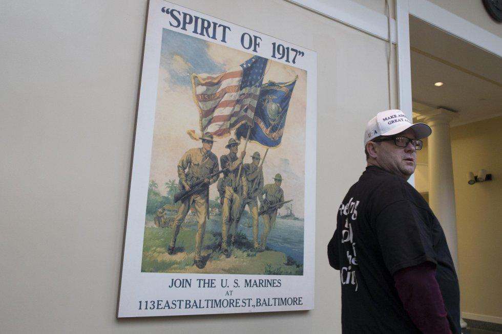 """Un asistente lleva puesta una gorra con el lema """"Hacer a América grande otra vez"""", mientras observa un cartel conmemorativo de la I Guerra Mundial."""