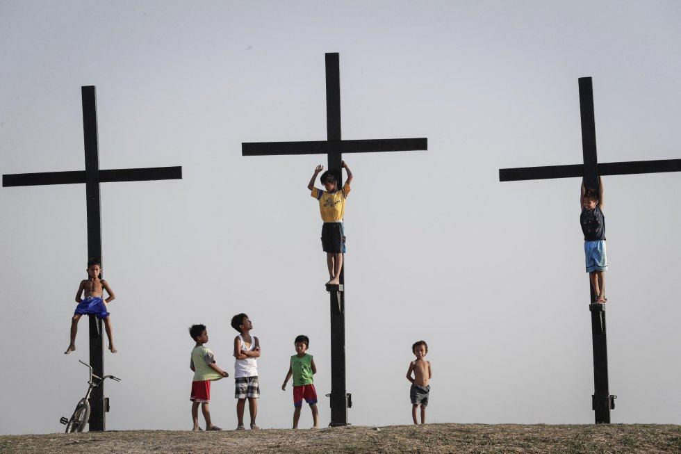 Varios niños juegan junto a las tres cruces que se utilizarán en la recreación de la crucifixión de Jesucristo, en la localidad de San Pedro Cutud, Filipinas.