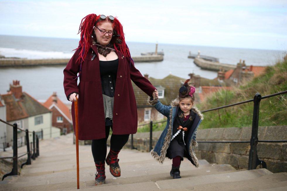 Goths Gemma Loveless y su hija Freya 6 de Manchester caminan para asistir al Goth Festival en Whitby