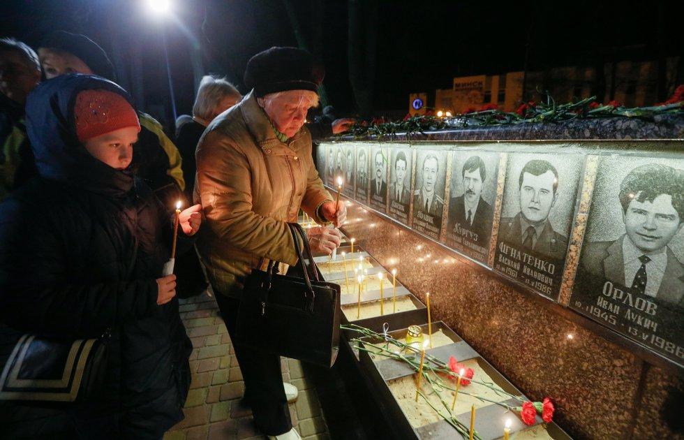 """Ucranianos rinden homenaje en el monumento a los """"liquidadores"""", a los trabajadores que murieron durante la limpieza de las obras después del desastre de la central nuclear de Chernóbil en Slavutich, Ucrania."""