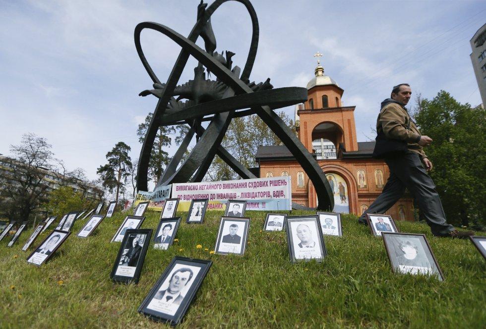 Fotografías permanecen junto al monumento a las víctimas del desastre de Chernóbil durante una ceremonia realizada en Kiev.