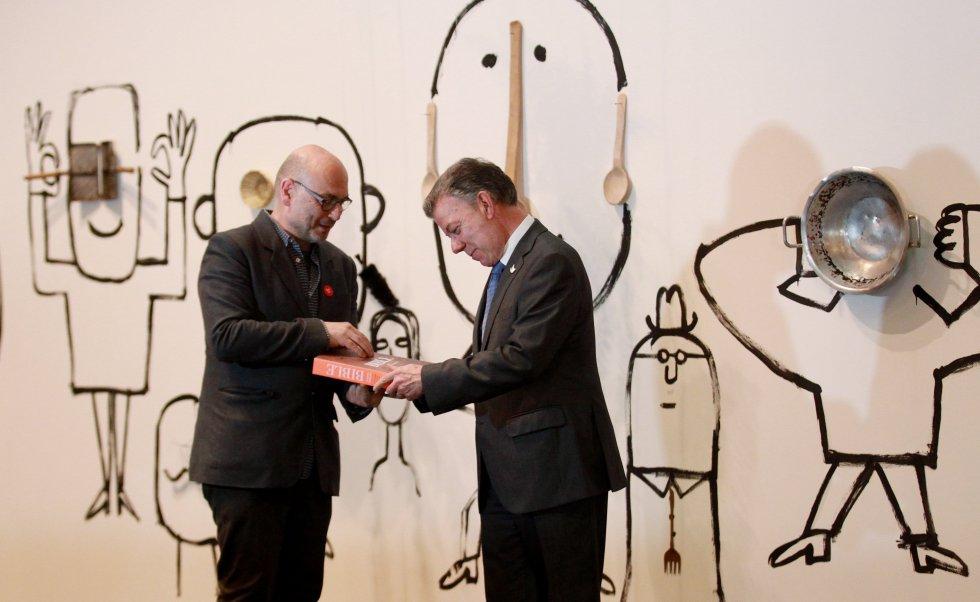 El presidente de Colombia, Juan Manuel Santos (d), recibe una biblia ilustrada por el dibujante e ilustrador francés Serge Bloch (i).