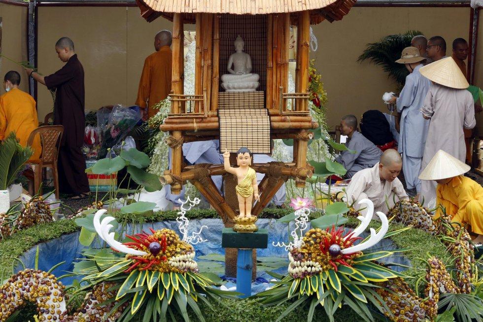 """Trabajadores vietnamitas terminan de preparar sus muestras para la celebración de """"Vesak"""", conmemoración del nacimiento, la iluminación y la muerte de Buda, en el lago Diyawanna Oya, cerca del Parlamento de Sri Lanka en Colombo."""