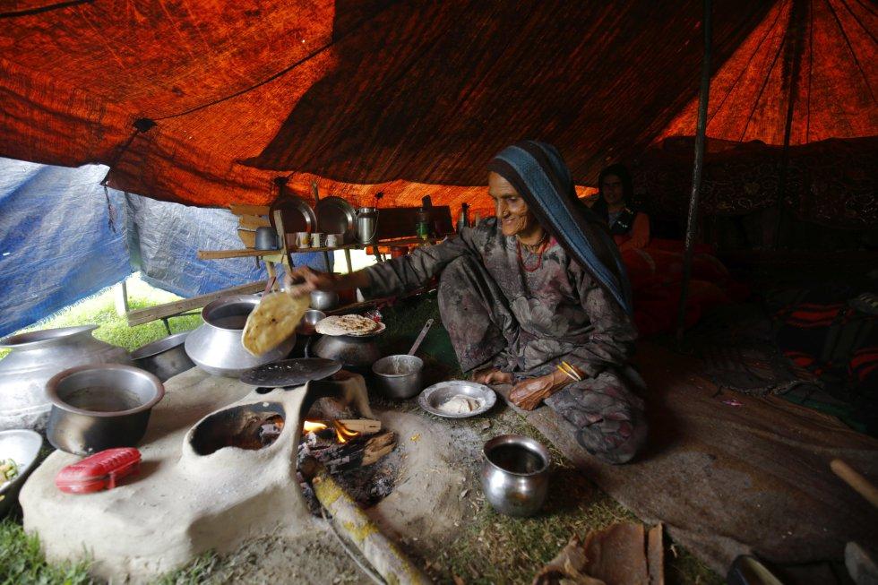 Mujer prepara comida para su familia dentro de un refugio temporal a las afueras de Srinagar.