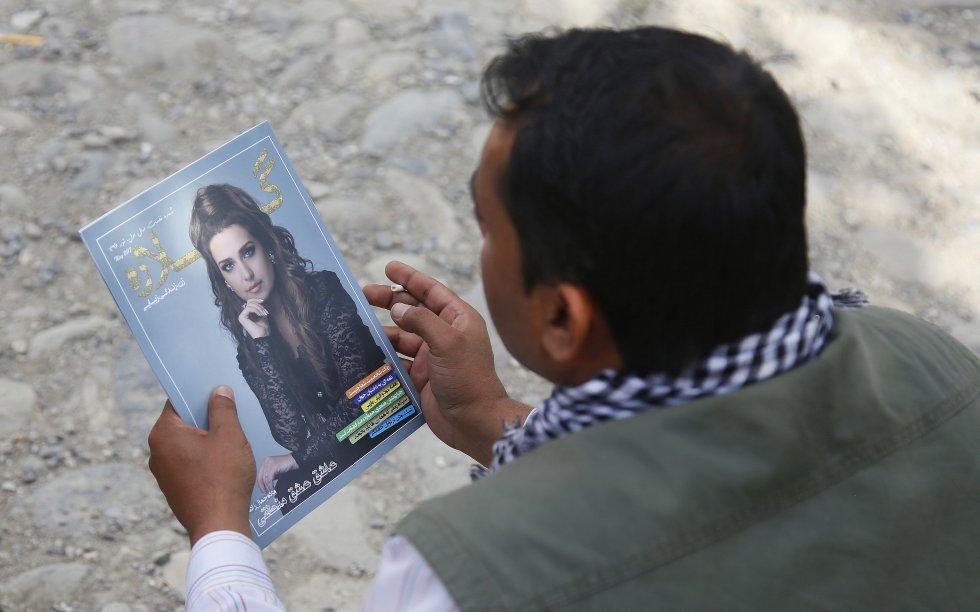 """Un ciudadano ojea un ejemplar de la primera revista femenina afgana """"Gellara""""."""