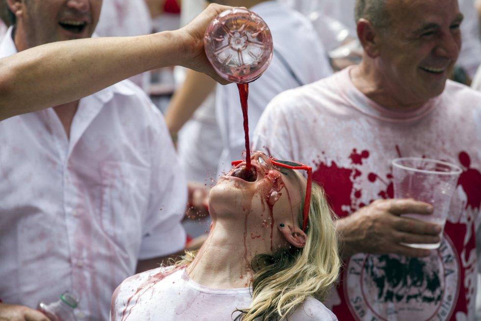 Una turista estadounidense bebe sangría tras el lanzamiento del tradicional chupinazo que ha abierto a las doce del mediodía las Fiestas de San Fermín 2017