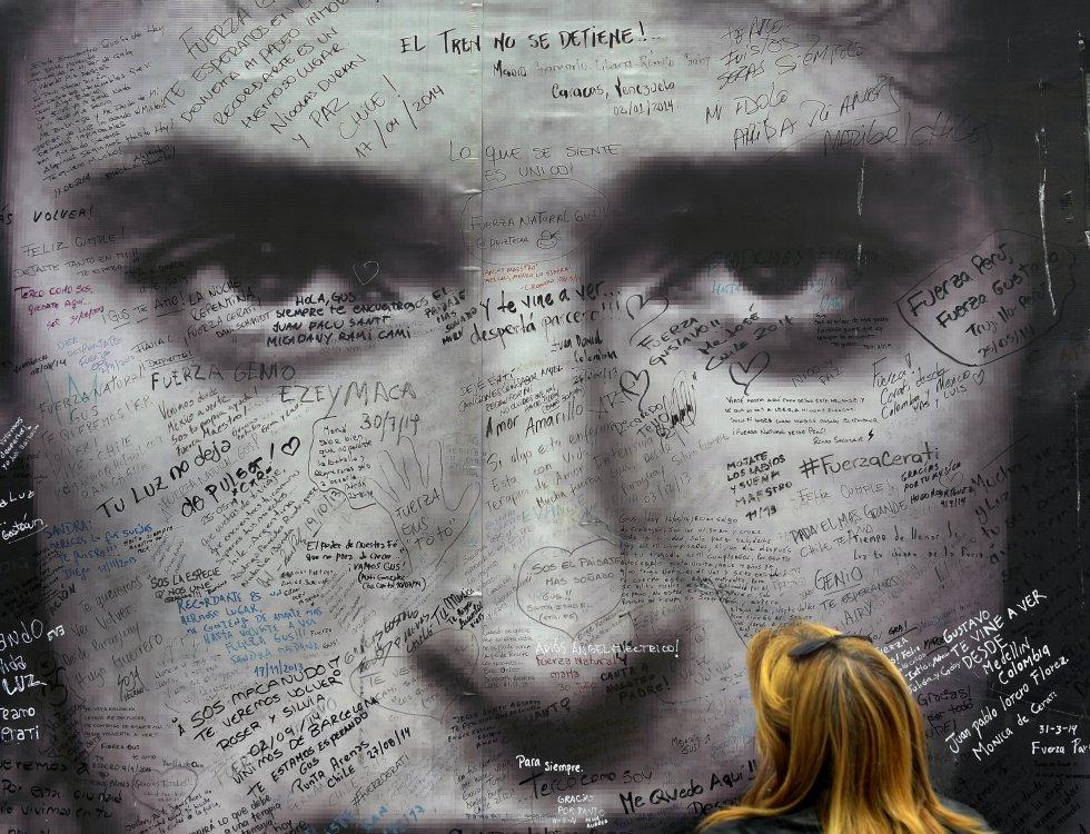 Una aficionada observa cartel de tributo a Gustavo Cerati, frente a la clínica donde murió el músico de un derrame cerebral el 4 de septiembre de 2014.