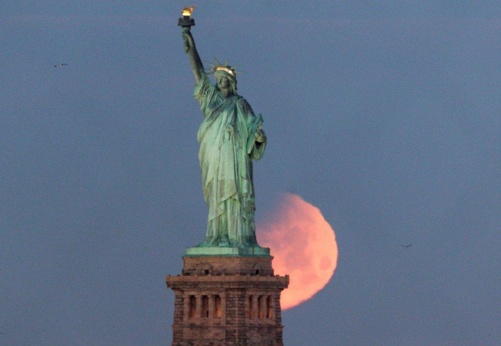 Vista de la luna tras la Estatua de la Libertad en Nueva York