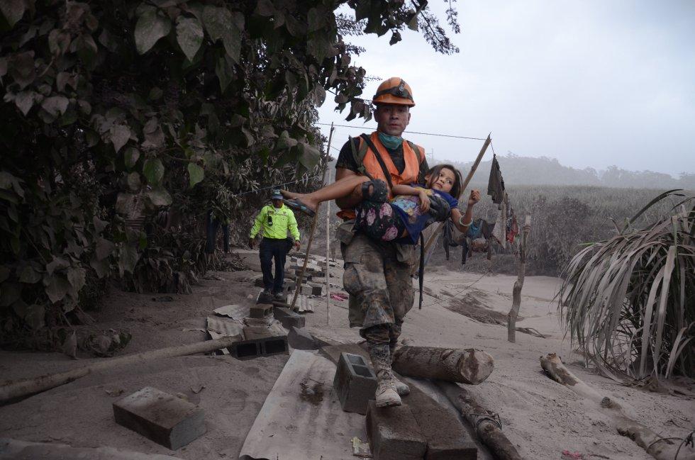 Un trabajador de los equipos de rescate de Guatemala ayuda a una niña en El Rodeo, Escuintla