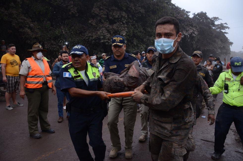 Un grupo de trabajadores de los equipos de rescate de Guatemala trasladan a un herido en El Rodeo, Escuintla