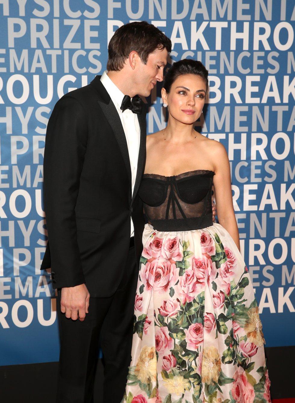 Mila Kunis y su esposo Ashton Kutcher en una alfombra roja