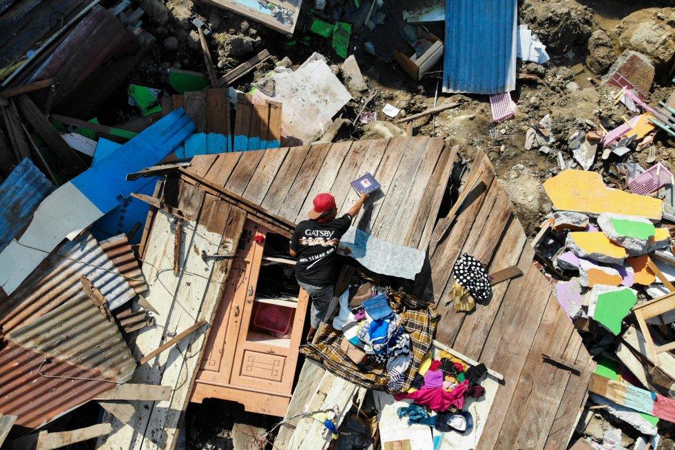Un hombre rescata artículos utilizables de los escombros de una casa destruida en Palu, Sulawesi Central de Indonesia, el 2 de octubre de 2018, después de que un terremoto y un tsunami azotaron el área el 28 de septiembre.