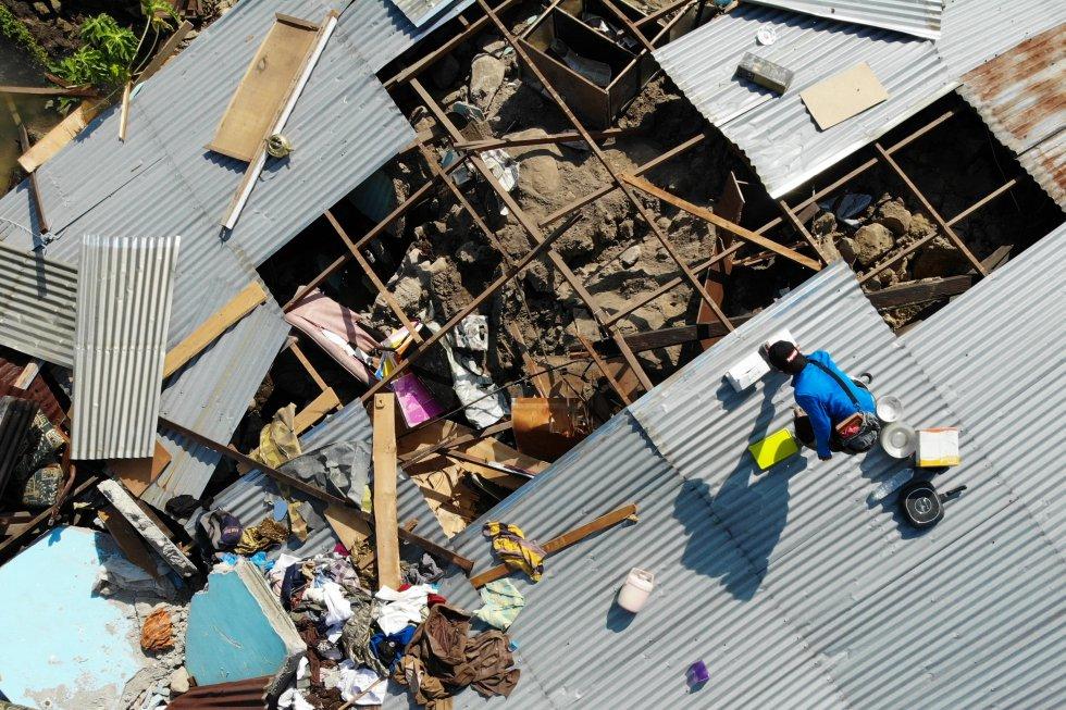 Los sobrevivientes rescatan artículos utilizables de los escombros de una casa destruida en Palu, Sulawesi Central de Indonesia, el 2 de octubre de 2018, después de que un terremoto y un tsunami azotaron el área el 28 de septiembre.