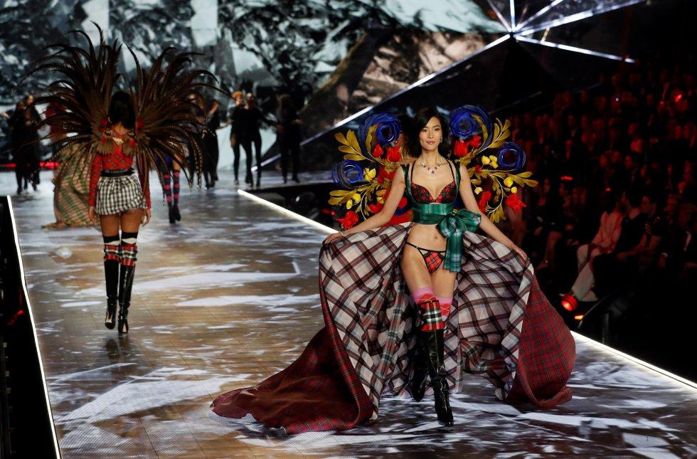 La modelo china Liu Wen (dcha) cruza la pasarela con un diseño de la firma de lencería Victoria's Secret en el ámbito del desfile de la marca en Nueva York