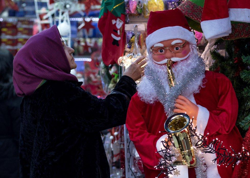 Varias personas realizan sus compras en un mercado decorado con motivos navideños en Estambul (Turquía)