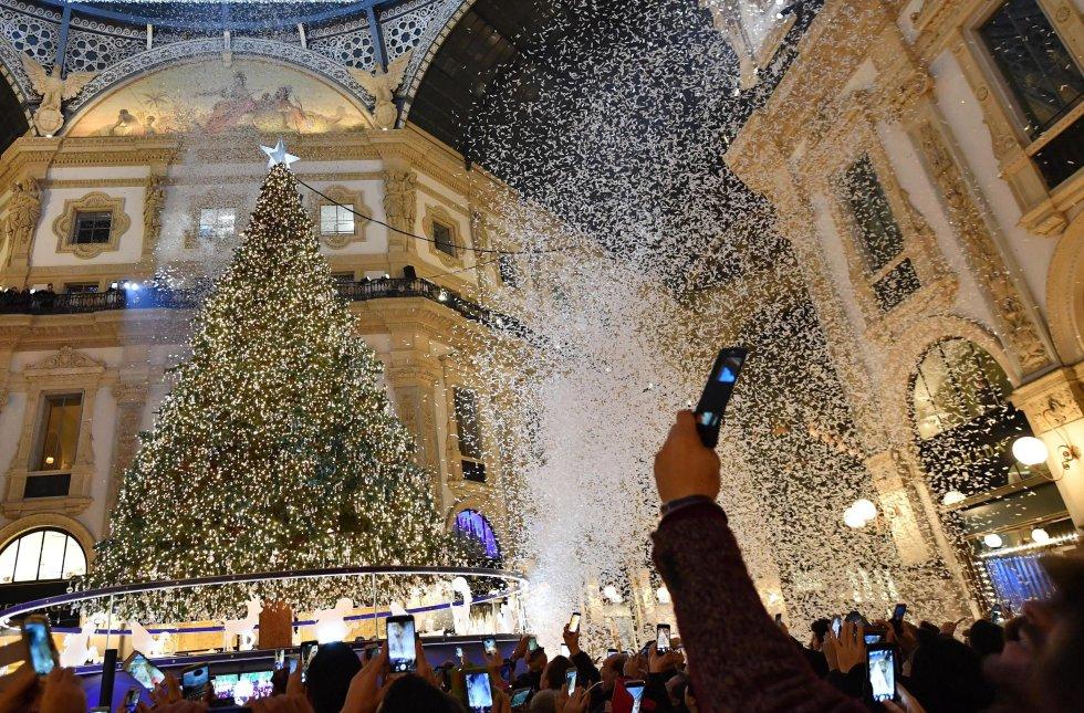 Una multitud toma fotografías durante la ceremonia en la que se han encendido las decoraciones navideñas, incluido el árbol de Navidad de Swarovski, en Milán (Italia)