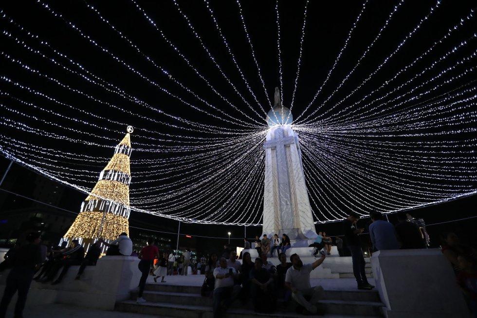 Un grupo de personas celebran el marco del inicio de las fiestas de navidad y de fin de año, en la plaza Salvador del Mundo, en San Salvador.