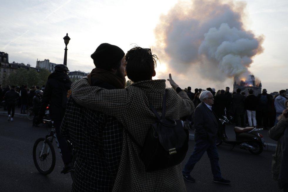 La multitud se aglutinaba a orillas del Sena, donde caían cenizas, tomando fotos con sus teléfonos en las que se veían la nube de humo amarillo, las cenizas, el pánico, la tristeza