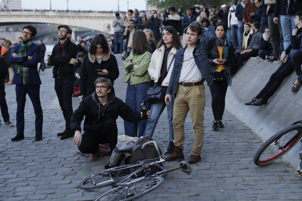 La multitud se aglutinaba a orillas del Sena, donde caían cenizas, tomando fotos con sus teléfonos en las que se veían la nube de humo amarillo, las cenizas, el pánico, la tristeza.