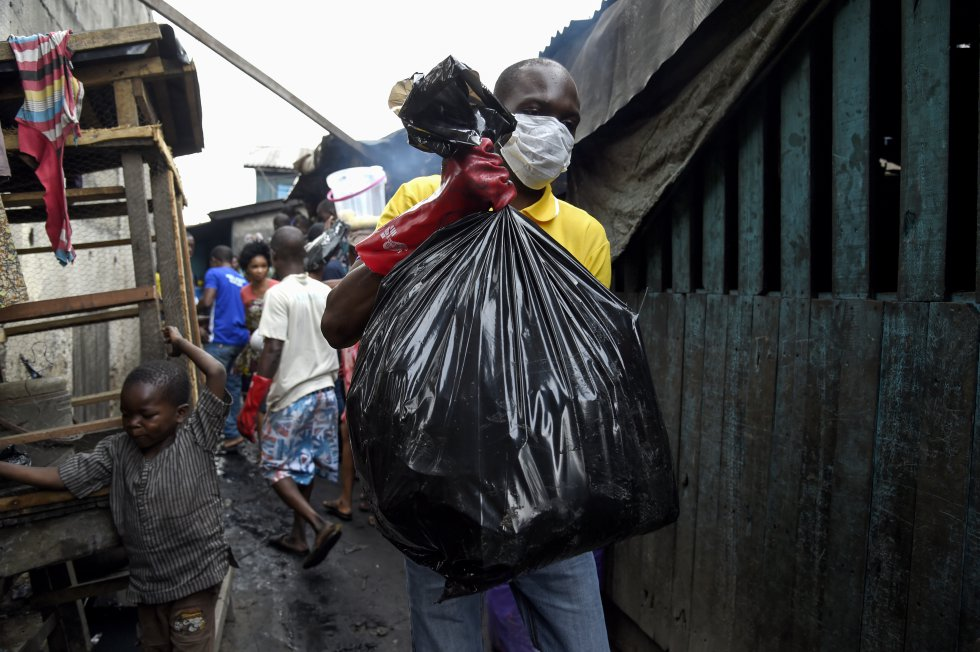 Nigeria. Un voluntario carga una bolsa de desechos en Makoko, uno de los barrios bajos más grandes del país.