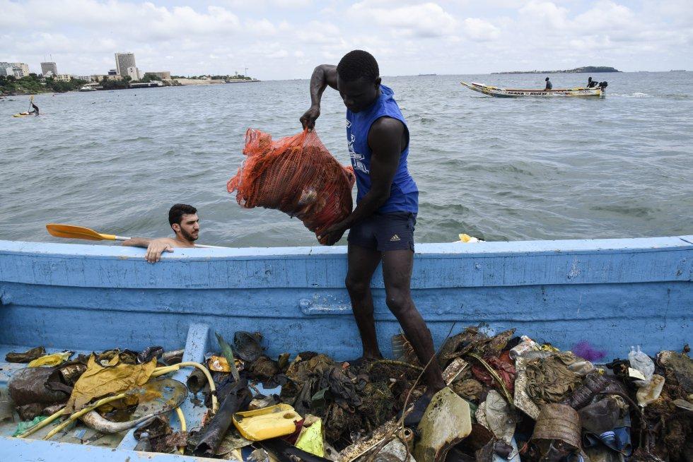 Senegal. Hombre ayudando a cargar la basura que es retirada del océano.