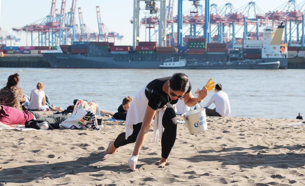 Alemania. Mujer ayuda a limpiar la playa.