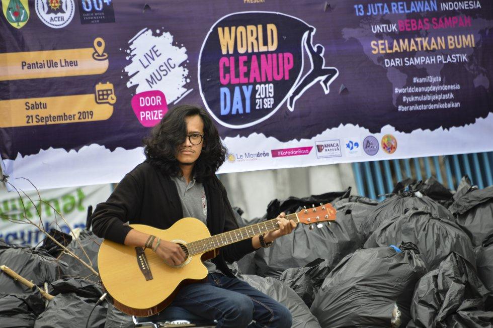 Indonesia. Estudiante hace presentación musical frente a bolsas de basura luego de acabar la limpieza.