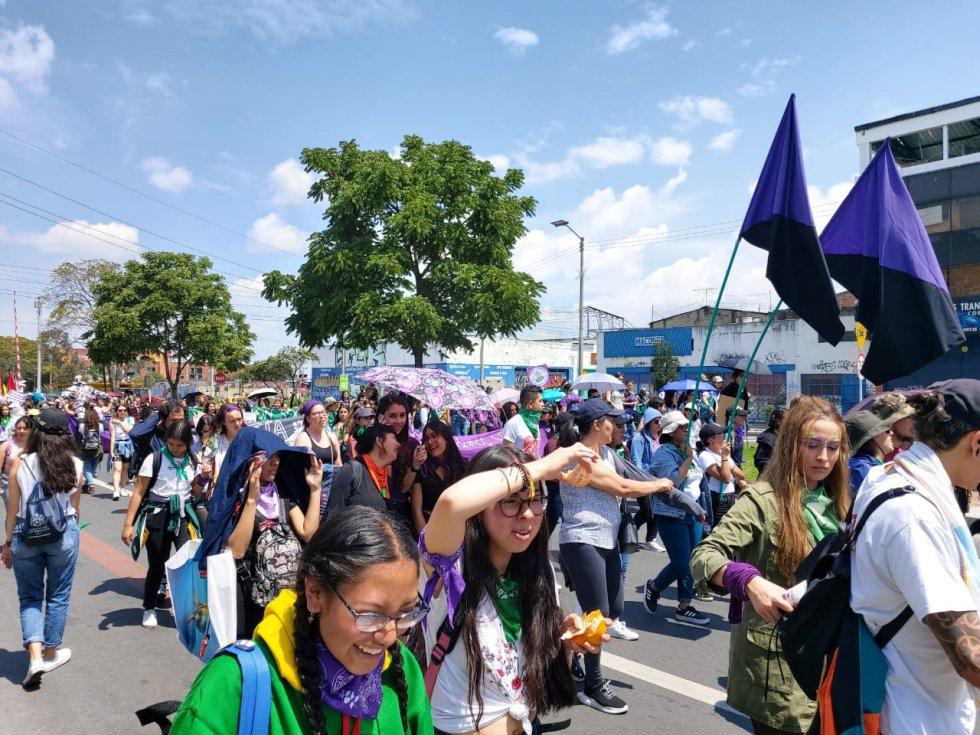 Con banderas moradas, varias mujeres marchan en su día.