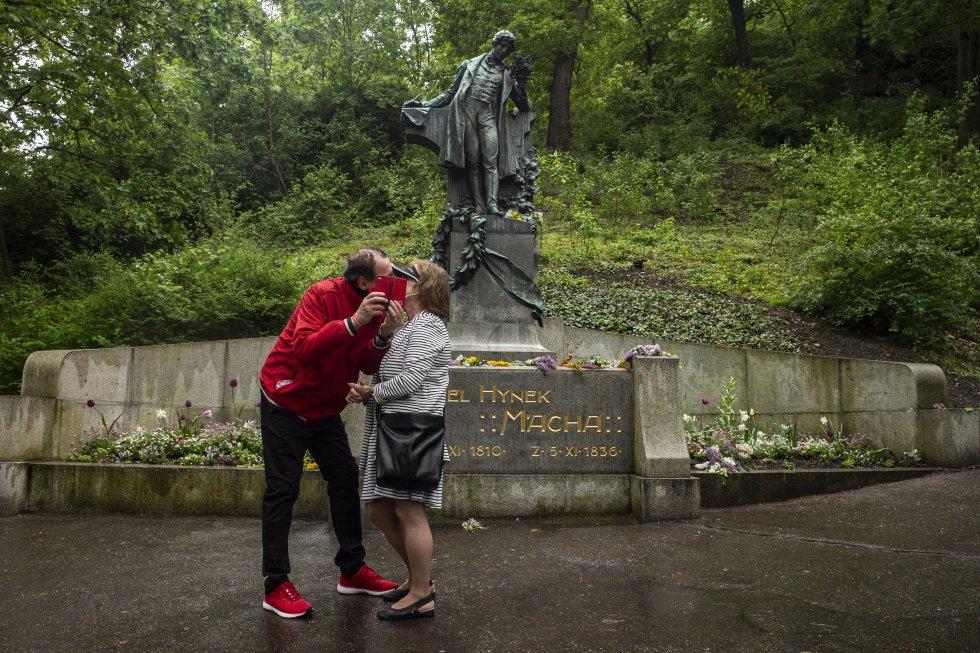 Una pareja se besa bajo la estatua del famoso poeta Karel Hynek Macha como parte de una tradición checa en la colina de Petrin