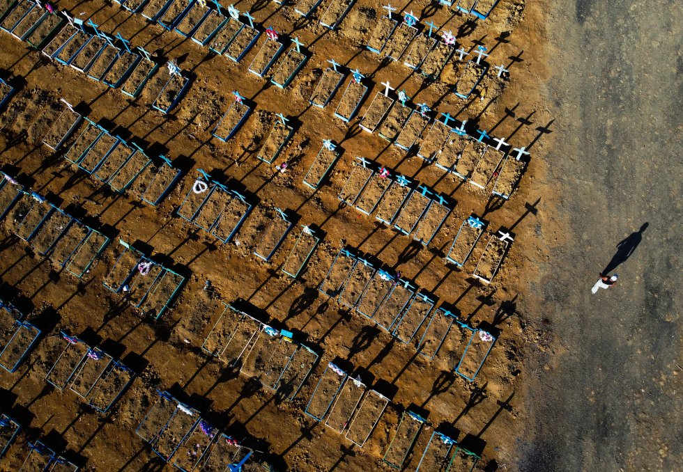 Vista aérea de un hombre caminando a través de un cementerio, donde han sido enterrados enfermos de COVID-19, en Brasil.
