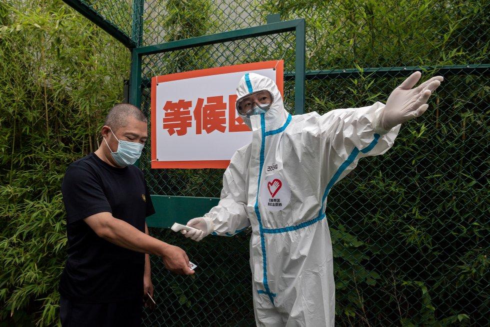 A un hombre le toman la temperatura en Beijing, mientras personal de la salud hace pruebas masivas en un parque para detectar el COVID-19.