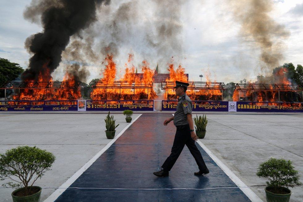 Un polícia camina frente a una pila de drogas ilegales que está siendo quemada como parte de una ceremonia para conmemorar el Día Internacional contra el Abuso de Drogas y Tráfico Ilícito.