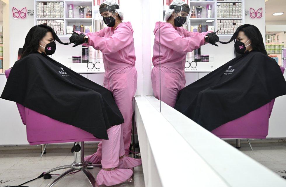En Bogotá, una peluquera atiende a su clienta teniendo en cuenta todas las medidas de protección contra el coronavirus.
