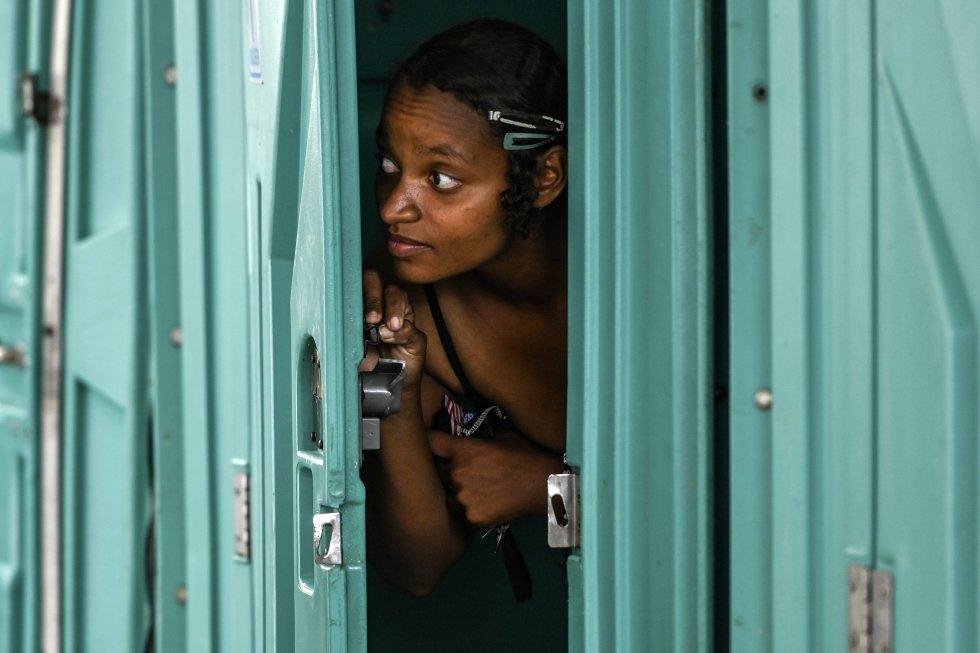 Una mujer está a punto de bañarse en una ducha portatil, ubicada en un área destinada a personas sin hogar, en Medellín.