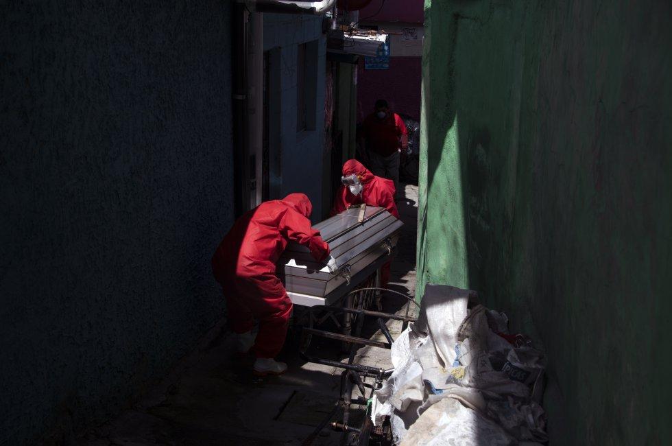 En El Salvador, trabajadores de una funeraria usan trajes de bioseguridad para transportar el cuerpo de un hombre de 75 años que murió, aparentemente, de coronavirus.